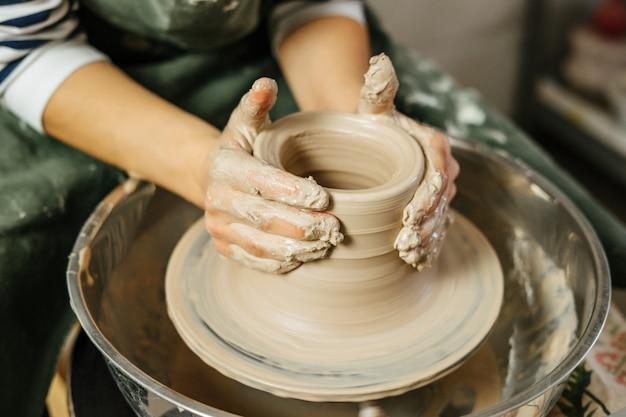 Ręki robi glinianemu garnkowi na kole garncarki garncarka. ceramika i ceramika na warsztatach.