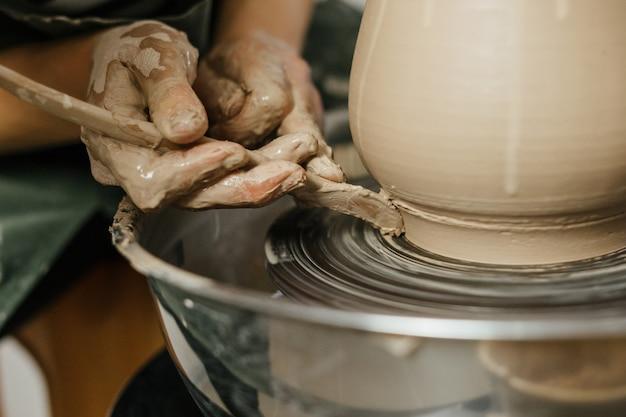 Ręki robi glinianemu garnkowi na kole garncarki garncarka. ręcznie robiony garnek w warsztacie ceramicznym. garncarstwo. umiejętności ceramiczne.