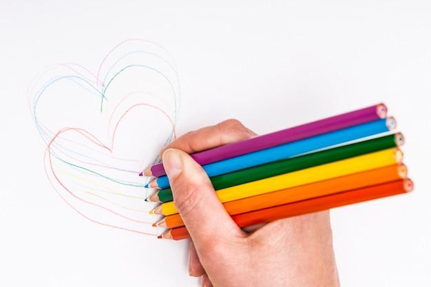 Ręki rysunkowi serca z barwionymi ołówkami