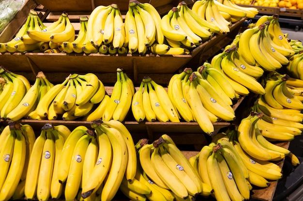 Ręki świezi żółci banany na drewnianych półkach w sklepach spożywczych