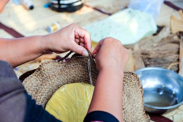 Ręki tajlandzcy żeńscy rzemieślnicy używają igielnego wyplatają szyć kapelusz