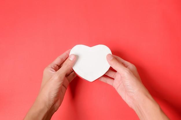 Ręki trzyma białego kierowego kształta prezenta pudełko na czerwonym tle. walentynki pudełko.