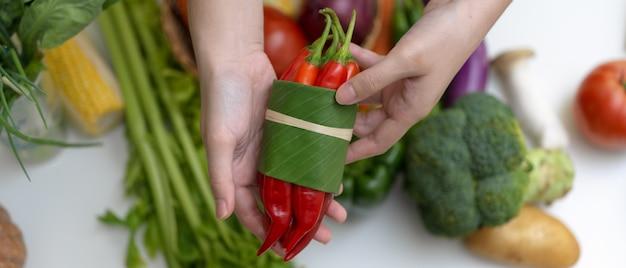 Ręki trzyma czerwonego chili pieprzu podczas gdy stojący przy stołem z innymi świeżymi rolnymi warzywami