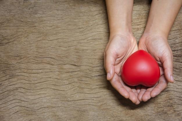 Ręki trzyma czerwonego serce na drewnianej desce