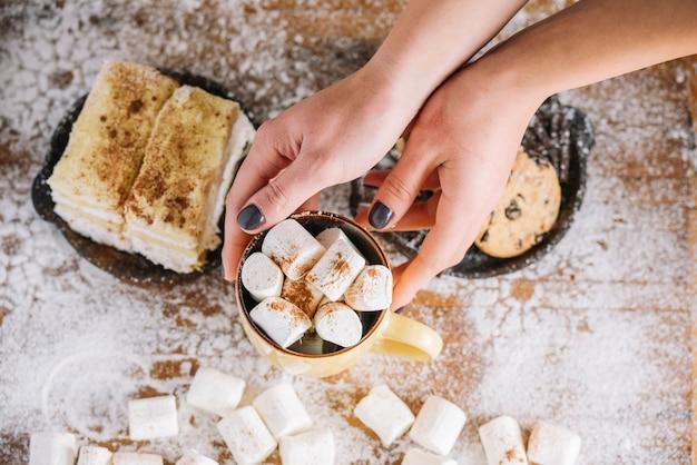 Ręki trzyma filiżankę z marshmallows blisko cukierki talerza