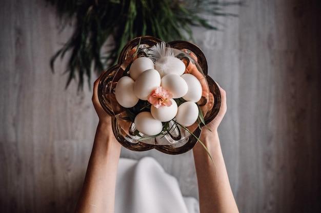 Ręki trzyma gęsich jajka na talerzu