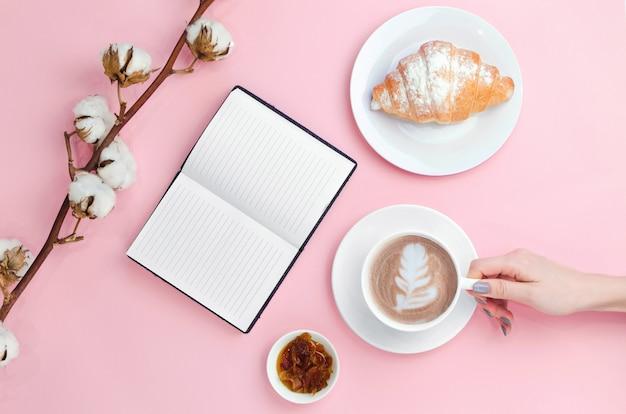 Ręki trzyma kawę i notatnika z rogalikiem i bawełny gałąź