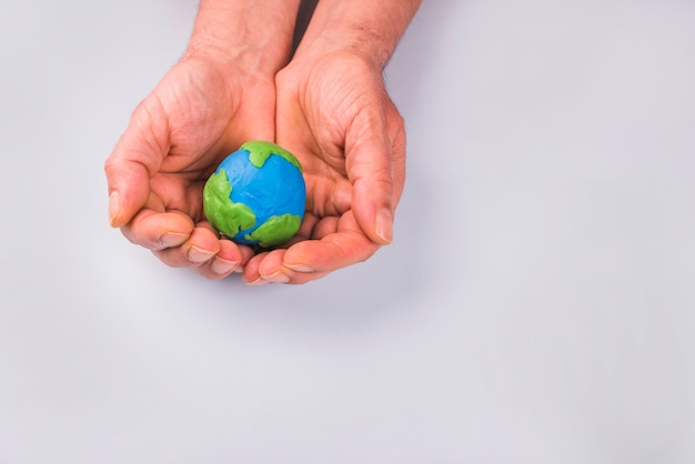 Ręki trzyma kolorowego glinianego model planety ziemia dziecko