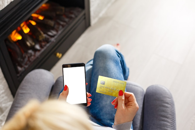 Ręki trzyma kredytową kartę i używa mobilnego mądrze telefon z rankiem