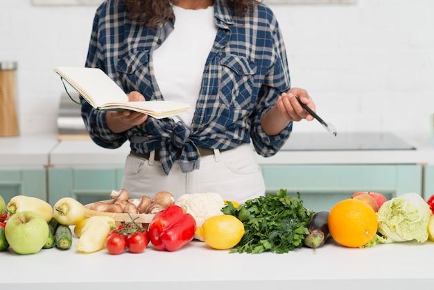 Ręki trzyma notatnika obok warzyw