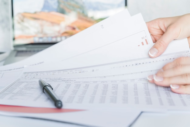 Ręki trzyma papiery z dane na biurku