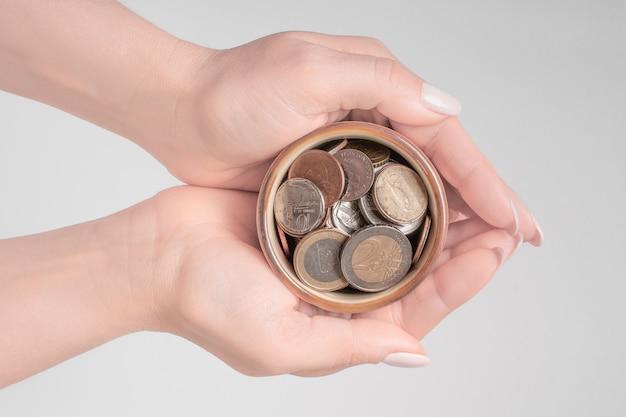 Ręki trzyma pieniądze słój na białym tle