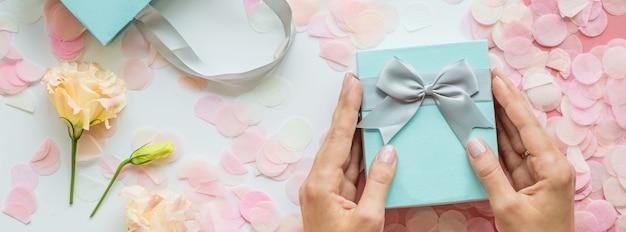 Ręki trzyma prezenta pudełka sztandaru tło