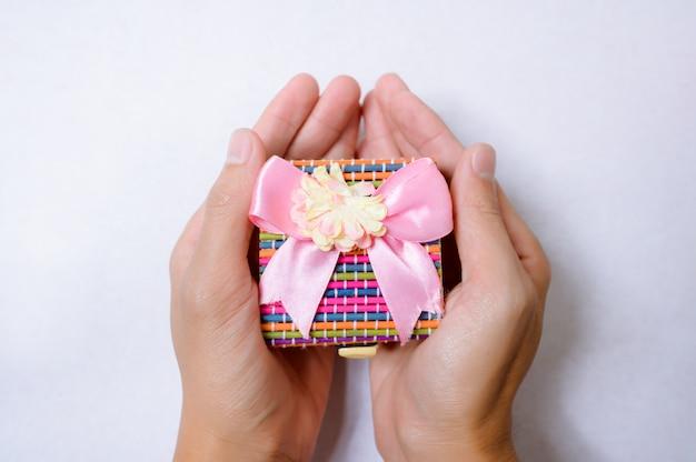 Ręki trzyma prezenta pudełko na białego tła odgórnym widoku.