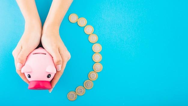 Ręki trzyma różowego prosiątko banka