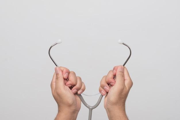 Ręki trzyma stetoskop i słowo na popielatym tle