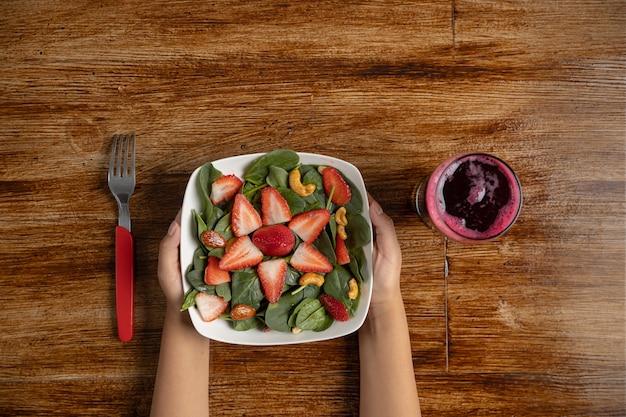Ręki trzyma truskawki i szpinaka sałatki na drewnianym stole i buraczkowym soku