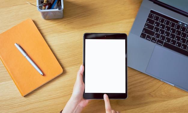 Ręki używać pastylkę z pustym ekranem z laptopem i akcesoriami na drewno stole.