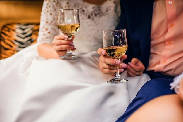 Ręki z szkłami szampański państwo młodzi przy ślubem