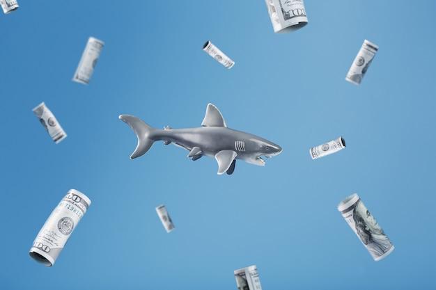 Rekin otoczony banknotami dolarowymi na niebieskim tle. konceptualny metaforyczny obraz groźnych drapieżników w biznesie i inwestowaniu