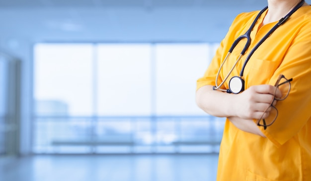 Reklama leku. młoda piękna dziewczyna w żółtym płaszczu z stetoskopem iz rękami skrzyżowanymi szpitalu. bezosobowe szerokie tło.