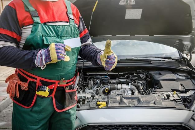 Reklama serwisu samochodowego. mechanik stojący w pobliżu samochodu pokazując kciuk do góry. samochód z otwartą maską