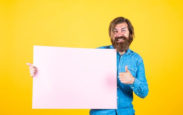 Reklama twojego produktu. ludzkie emocje. nieogolony facet z zadbanymi długimi włosami. fryzjer i fryzjer. męskie piękno i moda. szczęśliwy brodaty mężczyzna. brutalny kaukaski hipster trzymaj papier, miejsce na kopię.