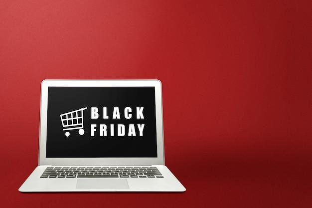 Reklama w czarny piątek na ekranie laptopa na kolorowym tle