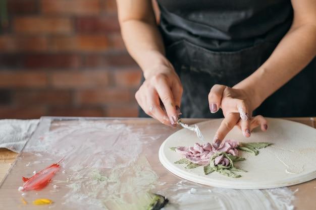 Rękodzieło ceramiczne. kompozycja kwiatowa w toku. kobieta rzemieślnicza z narzędziami do modelowania w miejscu pracy