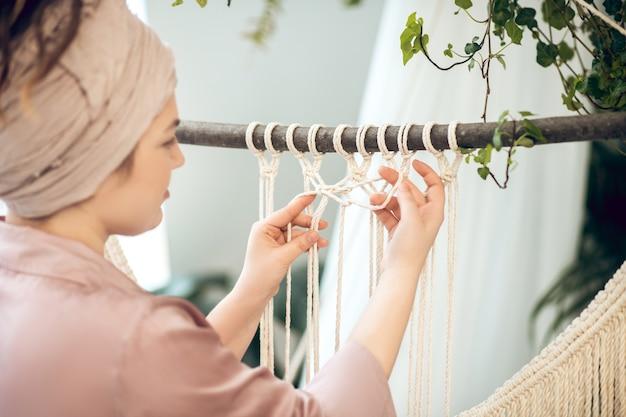 Rękodzieło. młoda kobieta w nakryciu głowy tkania makramy i wygląda na zaangażowanego