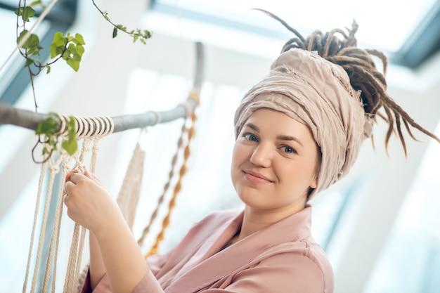 Rękodzieło. młoda kobieta w nakryciu głowy tkania makramy i wygląda pozytywnie