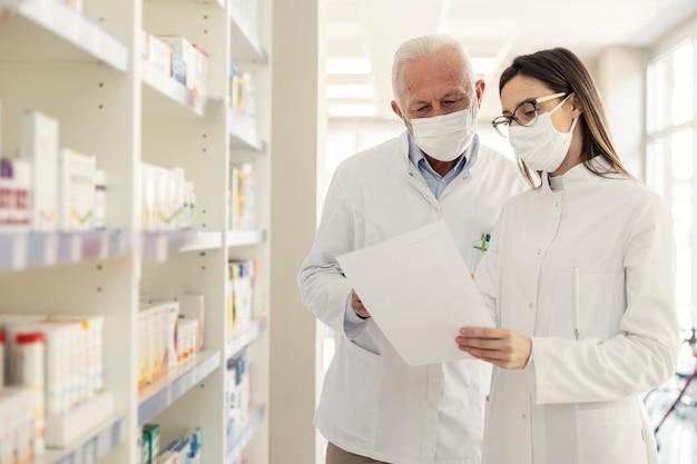 Rekomendacja farmaceuty a wirus koronowy. przed przejściem na emeryturę farmaceuta wyjaśnia młodemu farmaceucie dokumentację w aptece. noszą mundury i maski na twarz