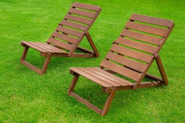 Rekreacja i reklama turystyczna dwa pusty leżak lub szezlong na trawie świeżego trawnika