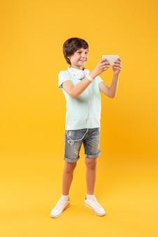 Rekreacyjne. zadowolony szczupły chłopiec w słuchawkach i robieniu selfie