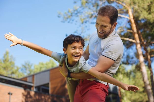 Rekreacyjne. zainspirowany brodaty mężczyzna uśmiecha się i bawi się z synem
