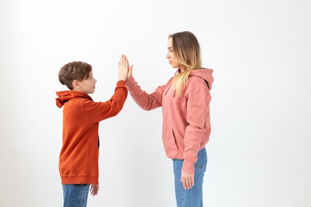 Relacja, dzień matki, dzieci i koncepcja rodziny - nastoletni chłopiec daje piątkę swojej mamie