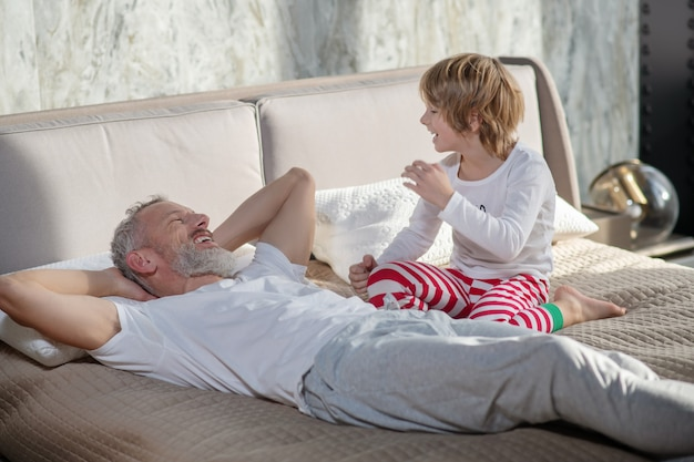 Relacja rodzic-dziecko. szczęśliwy uśmiechnięty tata leżący słuchanie i dziecko siedzące obok niego, rozmawiając na łóżku