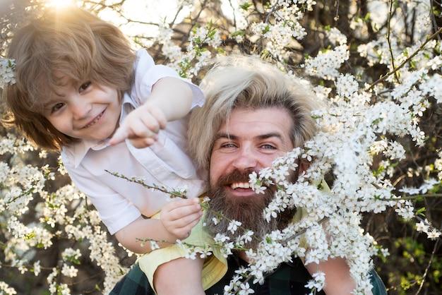Relacje i problemy rodzinne. dziecko z tatą w lecie parku. jazda na ramieniu.