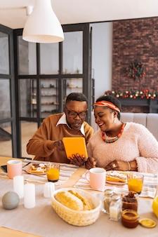 Relacje rodzinne. miły afro amerykanin siedzi razem z siostrą, pokazując jej zdjęcie na tablecie
