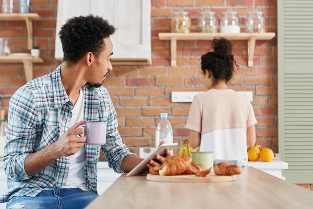 Relacje rodzinne, rutynowe pojęcie. ciemnoskóry mężczyzna rasy mieszanej afro american używa tabletu do komunikacji online