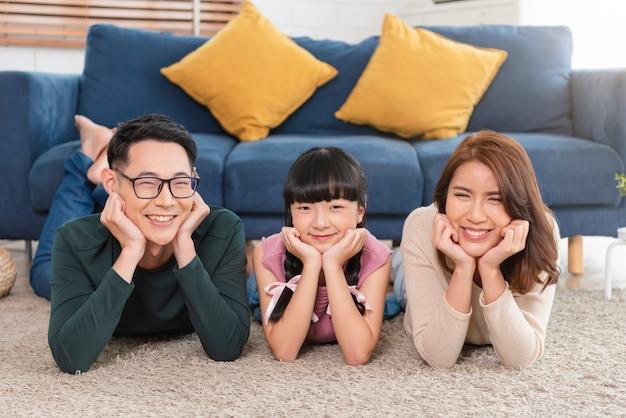 Relaks azjatyckiej rodziny z radością i uśmiechem na dywanie w salonie w domu.