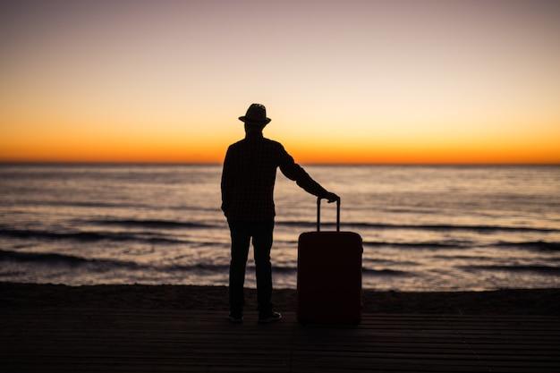 Relaks człowieka z walizką na plaży o zachodzie słońca sylwetka. koncepcja podróży wakacyjnych. facet z walizką na krajobraz oceanu.