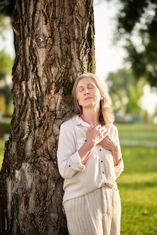 Relaks. dorosła spokojna kobieta z opadającymi powiekami w jasnym garniturze ze złożonymi dłońmi na klatce piersiowej, stojąca w pobliżu drzewa w parku