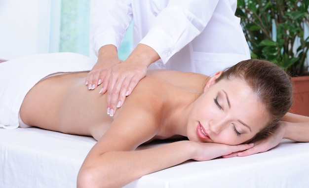 Relaks i masaż pleców dla pięknej ładnej dziewczyny w gabinecie kosmetycznym