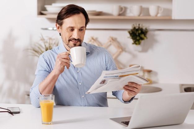 Relaks i praca w tym samym czasie. zadowolony inteligentny zaangażowany biznesmen siedzi w domu i pije herbatę, korzystając z laptopa i czytając czasopismo
