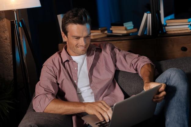 Relaks na kanapie. atrakcyjny młody człowiek zabawy pisząc list do swojego przyjaciela