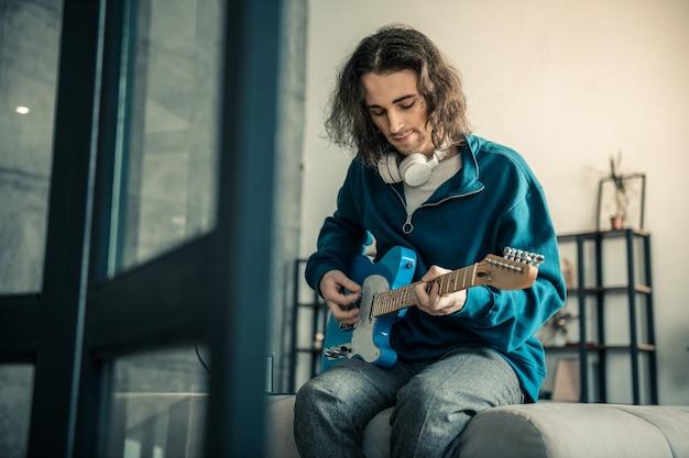 Relaks na kanapie. spokojny, przystojny facet z tatuażem na twarzy grający na gitarze podczas pobytu w salonie
