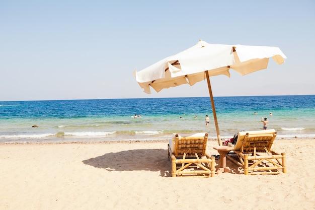 Relaks na plaży blisko morza, oceanu. z parasolem i dwoma krzesłami