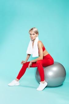 Relaks po treningu młoda piękna kobieta w odzieży sportowej z ręcznikiem na ramionach, siedząc na
