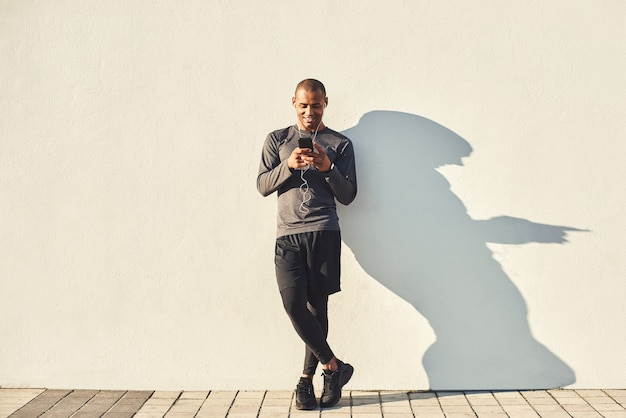 Relaks po treningu pełnej długości portret wesołego afrykańskiego sportowca robi sobie przerwę podczas